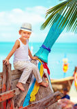 Cute kid, boy sitting on old boat on tropical beach Royalty Free Stock Photos