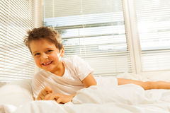 Cute kid boy smiling while lying on his bed Stock Image