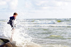 Cute kid or boy is splashed by the wave of sea Royalty Free Stock Photography