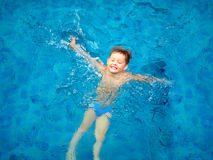 Cute kid, boy swimming in pool water, top view Stock Photos