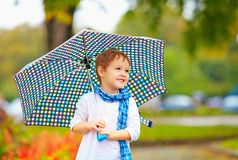 Cute kid boy with umbrella in autumn park Royalty Free Stock Image