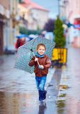 Cute kid, boy walking in puddle in rainy city. Cute kid, little boy walking in puddle in rainy city royalty free stock images