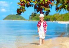 Cute kid boy walking in water on tropical beach Royalty Free Stock Images