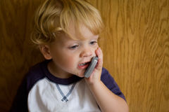 Cute Kid with Cell Phone. Cute little boy making a call on his cell phone Stock Photos