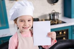 Cute kid in chef hat and apron holding blank card and smiling. At camera stock photography