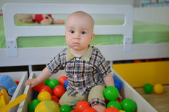 Cute kid or child playing colorful balls looking down Royalty Free Stock Photos