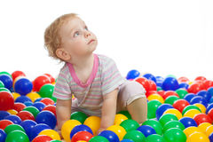 Cute kid playing colorful balls looking up Stock Photos