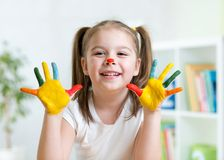 Cute kid child showing her hands painted in bright Royalty Free Stock Images