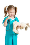 Cute kid with clothes of doctor with plush toy over white Royalty Free Stock Image