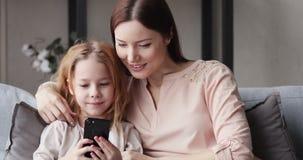 Cute kid daughter having fun with mom using smart phone