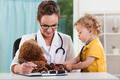 Cute kid diagnosing teddy bear Stock Photos
