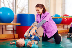 Cute kid with disability has musculoskeletal therapy by doing exercises in body fixing belts Stock Photo