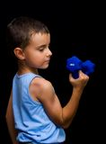 Cute kid doing fitness. Portrait of a cute kid exercising with weight lifting, isolated on black background Stock Photo