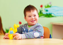 Cute kid with down`s syndrome playing in kindergarten Royalty Free Stock Image