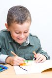 Cute kid drawing. Portrait of a cute schoolboy drawing Stock Images