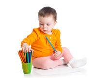 Cute kid drawing with colourful pencils Stock Image