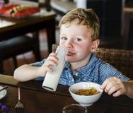Cute kid drinking milk for breakfast stock photography