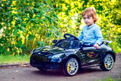 cute toddler boy ride on electric car in a park
