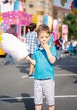 Cute kid eating cotton candy over fair background Stock Photo