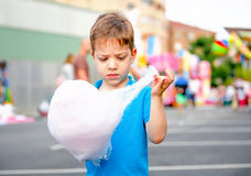 Cute kid eating cotton candy over fair background. Portrait of cute child eating cotton candy over a summer fair festival background Stock Photo