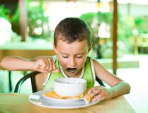 Cute kid eating soup. Portrait of a cute kid eating soup at a restaurant in a garden, outdoors Royalty Free Stock Photo