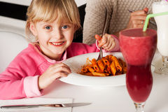 Cute kid enjoying pasta and watermelon juice Royalty Free Stock Photography