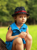 Cute kid in fashion hat sitting on green park Stock Photos