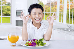 Cute kid with fresh salad shows OK sign Stock Photo