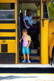 Cute kid is getting on the bus, ready to go to school Stock Image
