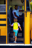 Cute kid is getting on the bus, ready to go to school Royalty Free Stock Photos