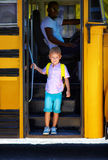 Cute kid is getting off the bus, after school Stock Photography