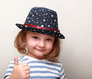 Cute kid girl in blue hat showing thumb up Royalty Free Stock Photo