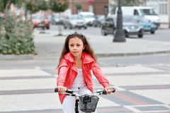 Cute kid girl in blue helmet going to ride her bike Stock Photo