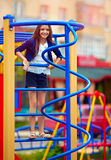 Cute kid, girl climbs on the stile at playground Stock Photos