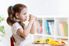 Cute kid girl drinking water in home. Cute kid girl drinking water sitting at table in home Royalty Free Stock Photo