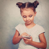 Cute kid girl with happy smile texting sms on mobile phone on bl. Ue background with empty copy spaceю Toned vintage portrait Stock Photography