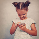 Cute kid girl with happy smile texting sms on mobile phone on bl. Ue background. Toned closeup portrait Royalty Free Stock Images