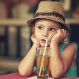 Cute kid girl in hat drinking apple juice in cafe and thinking a Stock Photos