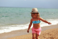 Cute kid girl in hat walking on the beach on sea background Stock Photos