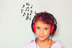 Cute kid (girl) with headphones having fun listening to music, and notes sketches Stock Photos