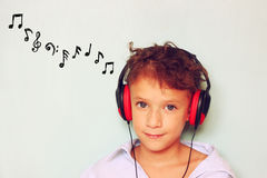 Cute kid (girl) with headphones having fun listening to music, and notes sketches. Royalty Free Stock Photos
