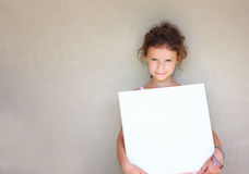 Cute kid (girl) holding blackboard standing against textured wall, retro filtered image. Stock Images