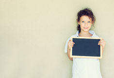 Cute kid (girl) holding blackboard standing against textured wall, retro filtered image. Royalty Free Stock Photography
