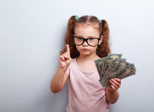Cute kid girl holding dollars and have an idea how earning much. Money in crisis. Serious child teaching in eyeglasses Stock Images