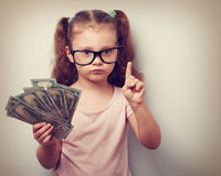 Cute kid girl holding dollars and have an idea how earning much. Money in crisis. Serious child teaching in eyeglasses. Vintage closeup portrait stock photo