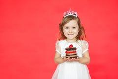 Cute kid girl holding a tasty mini cake Stock Image
