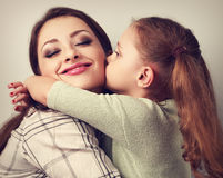 Cute kid girl kissing and cuddling her enjoying beautiful mother Stock Photography