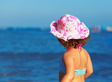 Cute kid girl looking on bright blue sea. Closeup Stock Photos