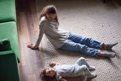 Cute kid girl lying on warm floor relaxing with mom royalty free stock images