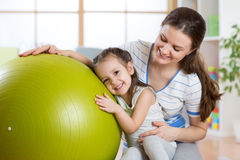 Cute kid girl  and mother with fitness ball. At home Stock Images